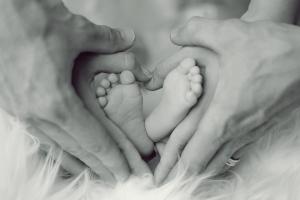 أيدي حول قدمي طفل على شكل قلب